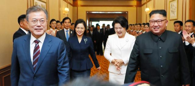 平壌の百花園迎賓館で18日、韓国の文在寅(ムンジェイン)大統領(左)と並んで歩く北朝鮮の金正恩(キムジョンウン)朝鮮労働党委員長(右)=平壌写真共同取材団撮影。金氏の妻、李雪主(リソルチュ)氏(左から2人目)や文氏の妻、金正淑(キムジョンスク)氏(同3人目)の姿も見える