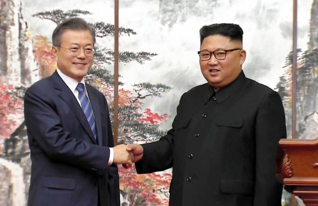 平壌で2018年9月19日、合意文書の署名式で握手する韓国の文在寅大統領(左)と北朝鮮の金正恩朝鮮労働党委員長。韓国KBSテレビから=AP