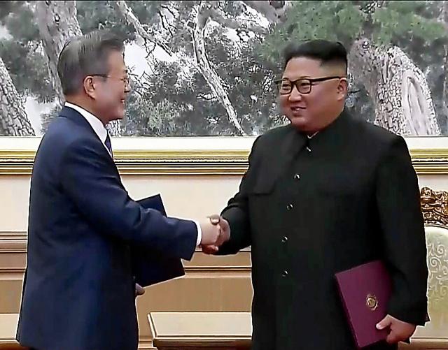 平壌の百花園迎賓館で19日、合意文書に署名して握手する韓国の文在寅大統領(左)と北朝鮮の金正恩朝鮮労働党委員長。韓国KBSテレビから=ロイター