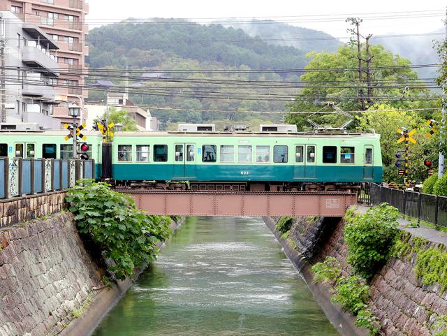 「夏虫色」と話題になった京阪の車両。2両編成で琵琶湖疏水にかかる橋の上をコトコト走る=大津市、高野良輔撮影