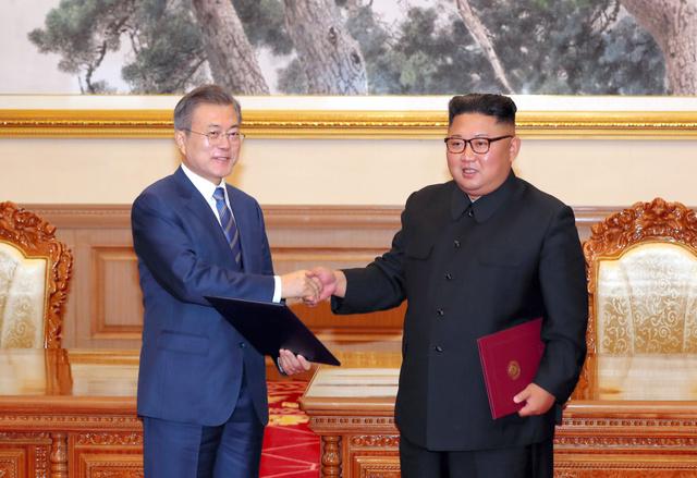 2018年9月19日、平壌の百花園迎賓館で「9月平壌共同宣言合意書」に署名し、握手する韓国の文在寅大統領(左)と北朝鮮の金正恩朝鮮労働党委員長=平壌写真共同取材団撮影