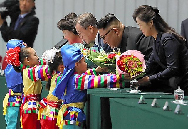 平壌のメーデー競技場で19日、マスゲームの観覧前に子どもたちから花束をもらう韓国の文在寅大統領夫妻と北朝鮮の金正恩朝鮮労働党委員長夫妻