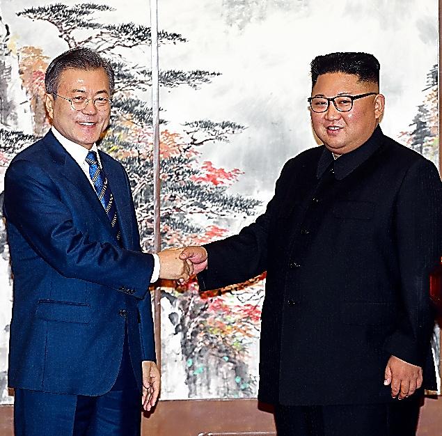 19日、共同記者会見で握手する韓国の文在寅大統領(左)と北朝鮮の金正恩朝鮮労働党委員長=平壌写真共同取材団撮影