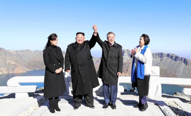 中朝国境にある白頭山で20日、手を掲げ合う韓国の文在寅大統領(右から2番目)と金正恩朝鮮労働党委員長(左から2番目)。両端は両首脳の夫人=平壌写真共同取材団撮影