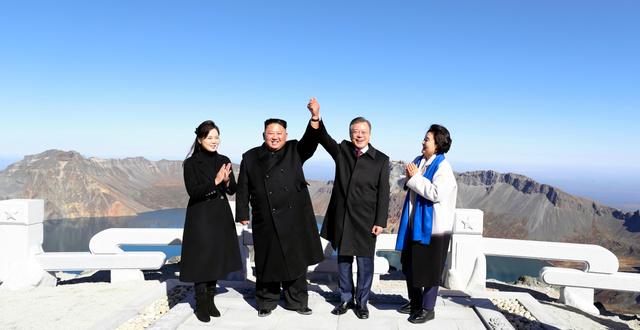 20日、中朝国境にある白頭山の山頂に立ち、握った手を上げてポーズをとる韓国の文在寅大統領(右から2人目)と北朝鮮の金正恩朝鮮労働党委員長(右から3人目)=平壌写真共同取材団撮影