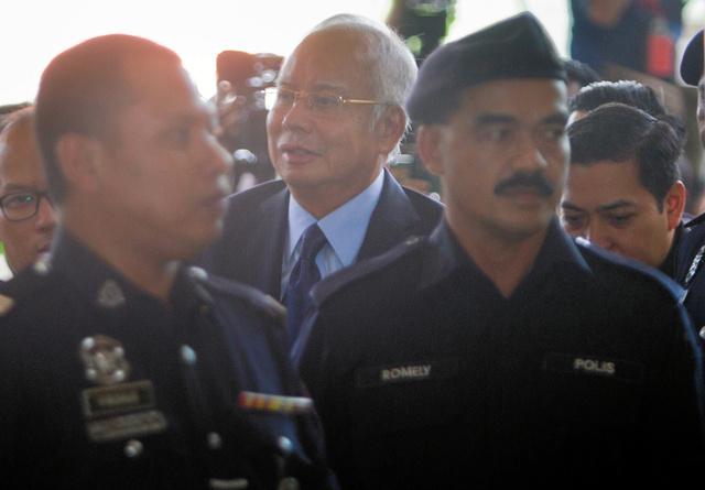 マレーシアの首都クアラルンプールで2018年9月20日、裁判所に入るナジブ前首相(中央)=AP