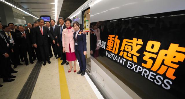 香港と中国本土を結ぶ高速鉄道の車両「動感号」の前で記念撮影する林鄭月娥・香港行政長官(右から2人目)=22日、香港・西…