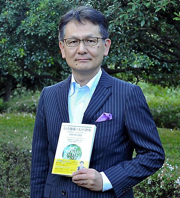 邦訳「小さな地球の大きな世界」を手にする谷淳也さん