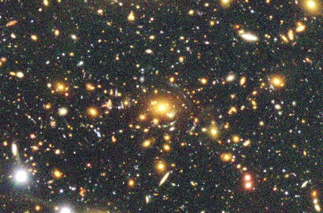 中央の銀河と「暗黒物質」によって光が曲がる重力レンズ効果。周囲の小さな銀河が同心円状に引き延ばされて見える(国立天文台提供)