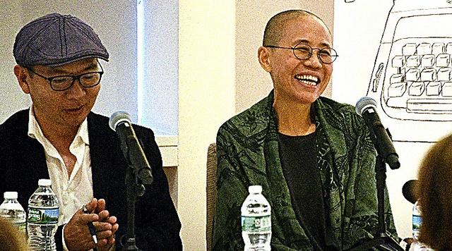 ニューヨークで行われた討論会の冒頭、笑顔を見せる劉霞氏(右)=26日、鵜飼啓撮影