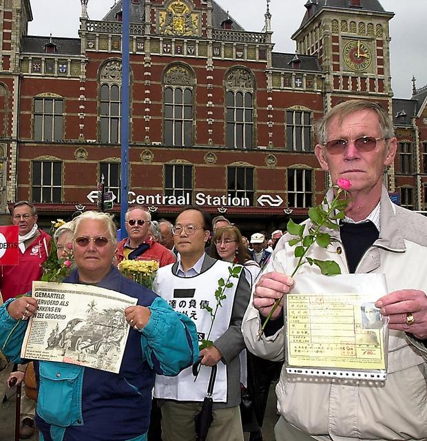 両陛下がオランダに到着した日、日本に謝罪と補償を求めてデモ行進する戦争被害者ら=2000年5月23日、アムステルダム中央駅前