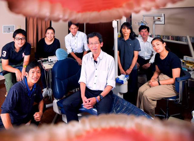 五島朋幸さん(中央)と新宿食支援研究会のワーキンググループのメンバー。口から食べる大切さを表現しようと、歯列模型越しに撮らせてもらった=東京都新宿区のふれあい歯科ごとう