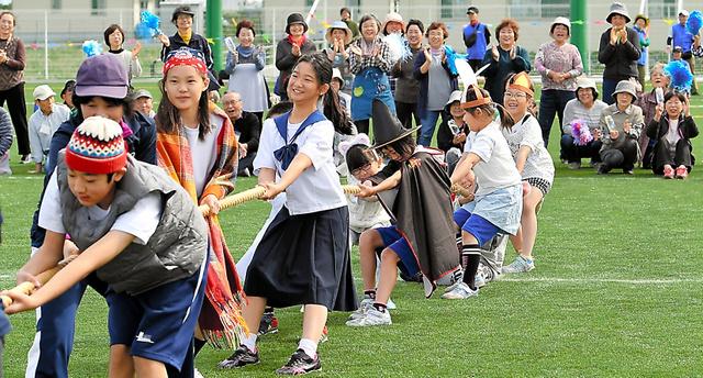 綱引きをするなみえ創成小・中学校の子どもたち。運動会には地域住民も参加し、声援を送った=13日午前、福留庸友撮影