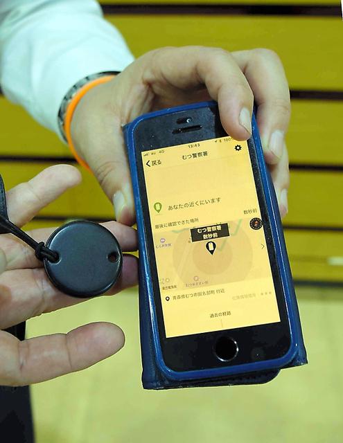 見守り支援の専用アプリが入ったスマホと丸型の発信器