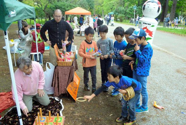 輪投げを楽しむ子どもたち。鳴子温泉から張りぼてのこけしもやってきた=仙台市青葉区の西公園