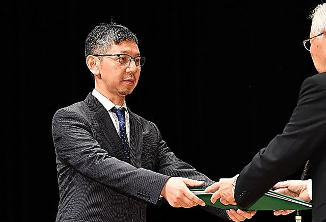 新聞協会賞の授賞式で表彰される大阪本社社会部の羽根和人次長=16日午後、仙台市青葉区