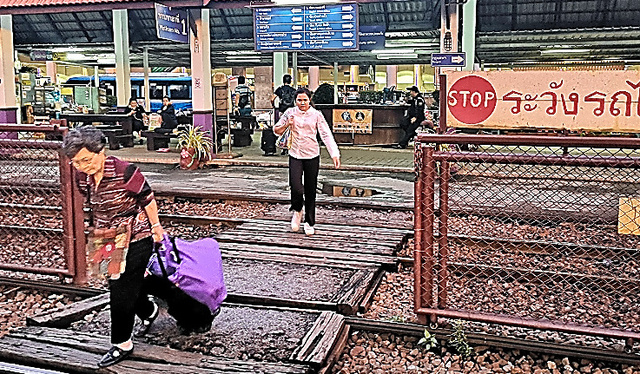 線路を歩いて渡る人たち=16日、バンコク・ドンムアン駅