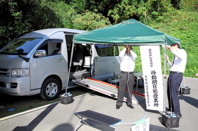 移動期日前投票所を「組み立てる」町選管の関係者ら。ワゴン車前の簡易テントも雨の日のピクニックっぽい=福島県田村市