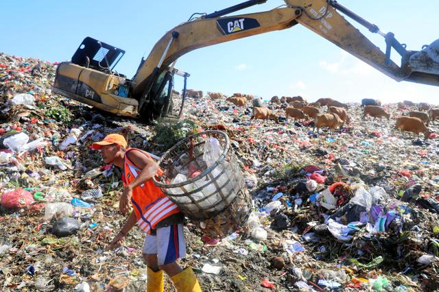 バリ島のゴミ集積場で、散乱したプラスチックごみを転売するために拾う人たち=6月15日、野上英文撮影