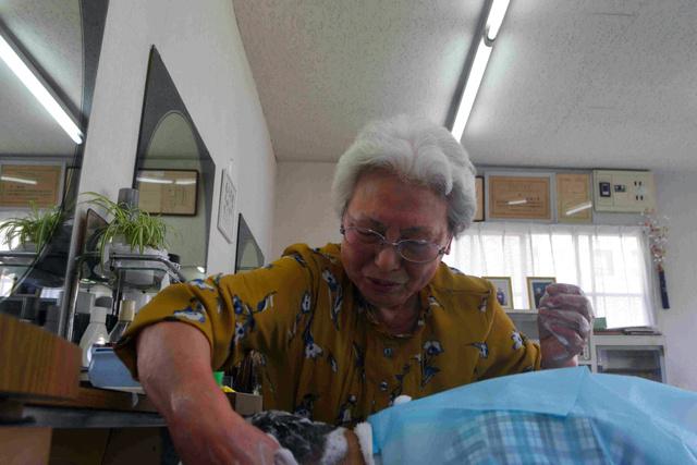 最後のお客にシャンプーをする村田一子さん=2018年10月28日、仙台市青葉区の理容「すずらん」