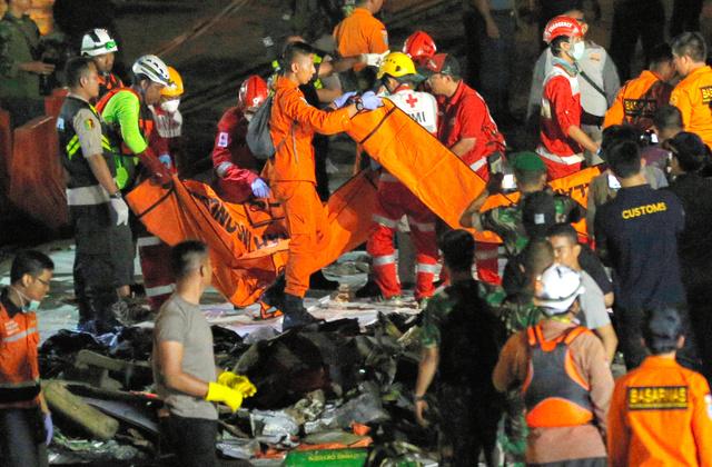 ライオン航空機の墜落現場付近で見つかった遺体や物品などを運ぶインドネシアの救急隊員ら=2018年10月29日、ジャカルタのタンジュンプリオク港、AP