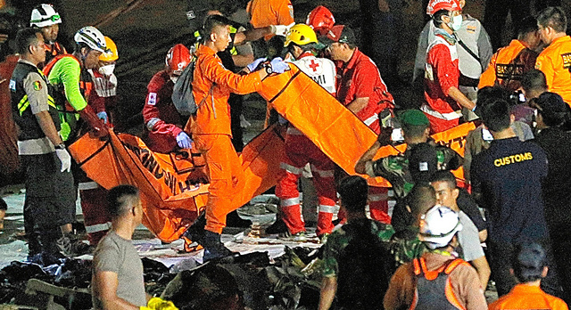 ライオン航空機の墜落現場付近で見つかった遺体や物品などを運ぶインドネシアの救急隊員ら=29日、ジャカルタのタンジュンプリオク港、AP