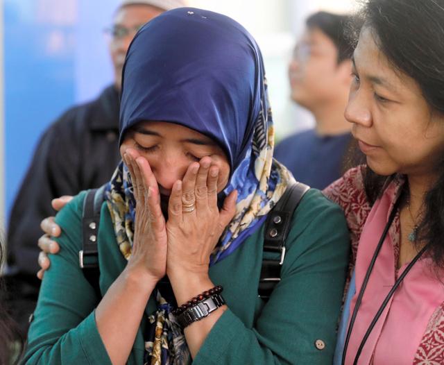 墜落機に夫が乗っていたエカさん(左)。遺体が運ばれる警察病院を訪れた=2018年10月30日、ジャカルタ、野上英文撮影