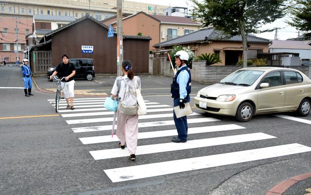 横断歩道の手前で車を止め、歩行者の安全を確保する警察官=2018年9月14日午前8時3分、北九州市戸畑区、島崎周撮影(車のナンバーにモザイクをかけています)