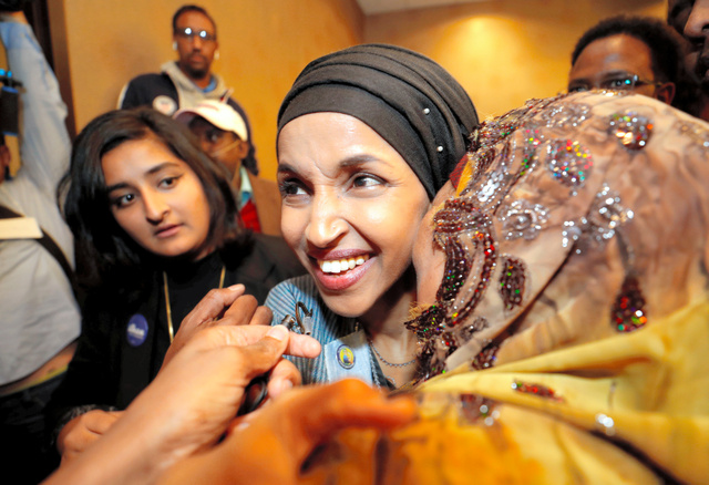 米ミネソタ州で6日、親族に抱きしめられる民主党候補のイルハン・オマール氏。初の女性イスラム教徒の下院議員となる1人になった=ロイター