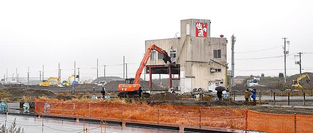 重機で解体される佐々直の旧本店工場。周囲では今も復興工事が続く=9日午前、宮城県名取市閖上、福留庸友撮影