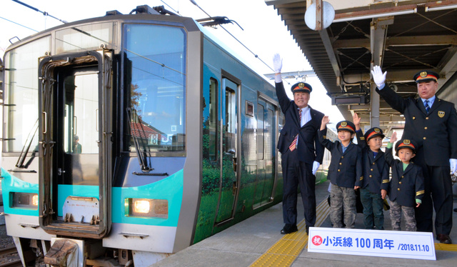 電車に出発の合図を出すJR西日本の沢谷英毅・敦賀地域鉄道部長(右端)と子どもら=2018年11月10日、福井県若狭町の…