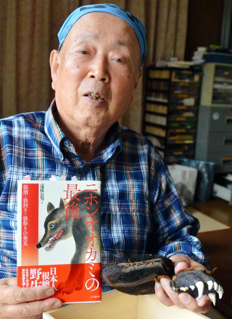 著書を持ち「子供の頃からオオカミに興味があった」と話す遠藤さん。左手に持つのはニホンオオカミと判定された骨=宮古市津軽石