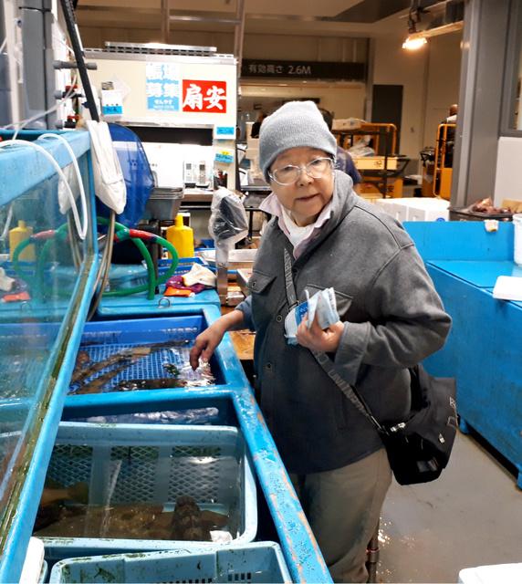 市場の地図を片手に魚を目利きする星喜久江さん