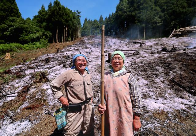 焼き終えたばかりの畑の前に立つ後藤勝利さん、清子さん夫妻=8月20日、山形県鶴岡市