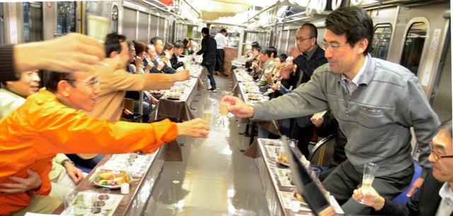 発車した電車内で乾杯する乗客=近江鉄道本線