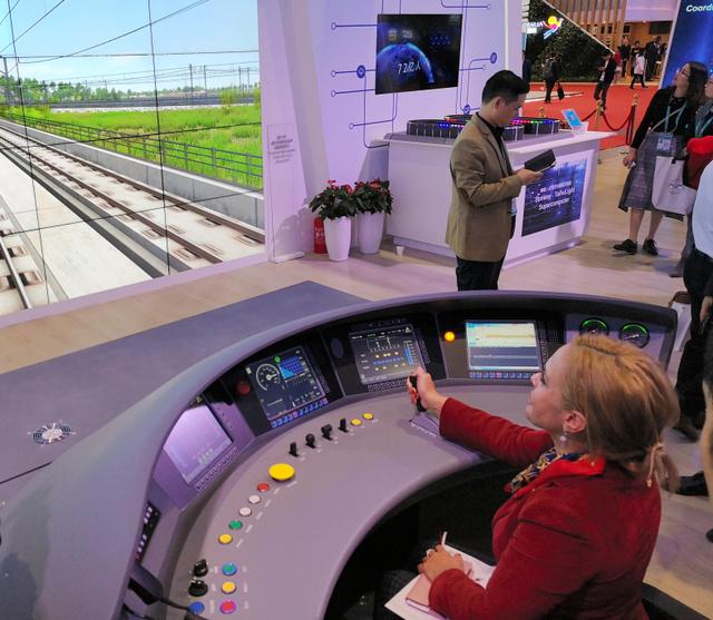 中国国際輸入博覧会の中国国家展のコーナーで、高速鉄道「復興号」のシミュレーターを楽しむ外国人の来場者ら。習近平国家主席も各国の首脳を案内した=2018年11月6日、上海市、吉岡桂子撮影