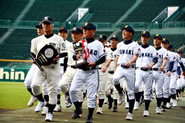マスターズ甲子園の開会式で優勝カップと準優勝盾を手に入場行進する北海道選抜チームの選手たち=10日、阪神甲子園球場
