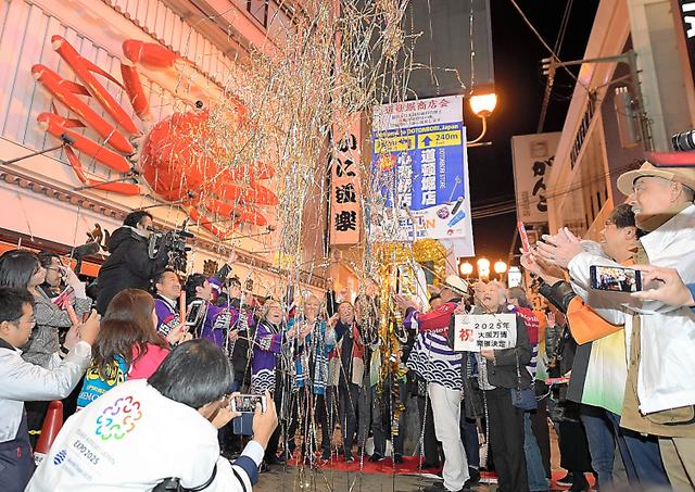 大阪万博の開催が決まり道頓堀でくす玉を割って喜ぶ人たち=24日午前1時8分、大阪市中央区、加藤諒撮影
