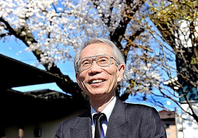 自宅前で桜の木を背に、笑顔で撮影に応じる大沼保昭さん=2014年