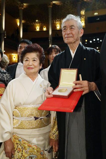 ノーベル賞授賞式を終え、医学生理学賞のメダルと賞状を手に撮影に応じる本庶佑・京都大特別教授(右)と妻の滋子さん=10日、ストックホルム、代表撮影