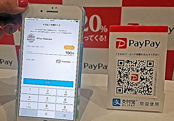 店舗側が表示するQRコード(右側)をスマホで読み取り、金額を入力すると決済が完了する=11月22日、東京都渋谷区