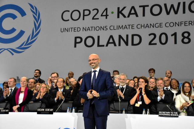 パリ協定の運用ルールを採択後、壇上で祝うCOP24の議長を務めたポーランドのクリティカ環境副大臣(中央)と各国の閣僚ら=15日、ポーランド南部カトビツェ、香取啓介撮影