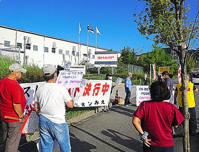 シャープの亀山工場前で抗議の声をあげる日系の労働者ら=三重県亀山市