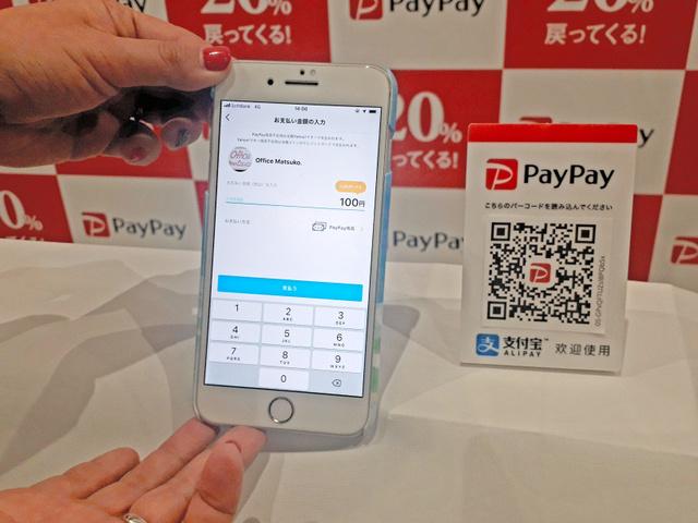 ペイペイでは、店側が表示するQRコード(右側)を客がスマートフォンで読み取り、金額を入力すると決済が完了する=東京都渋谷区
