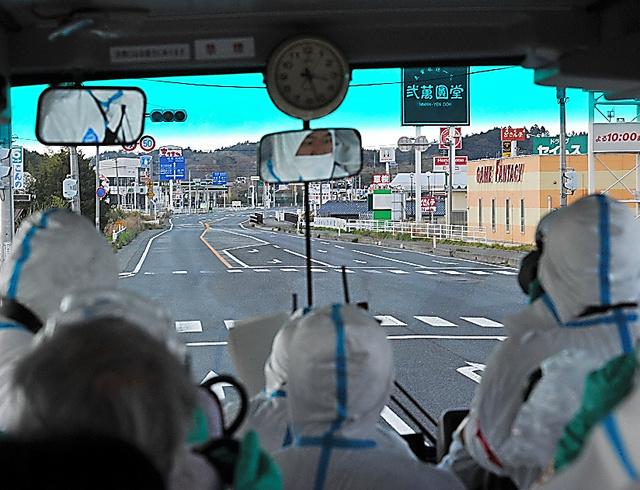 人気のない福島県浪江町をバスの中から見る報道関係者ら=2011年4月25日、相場郁朗撮影