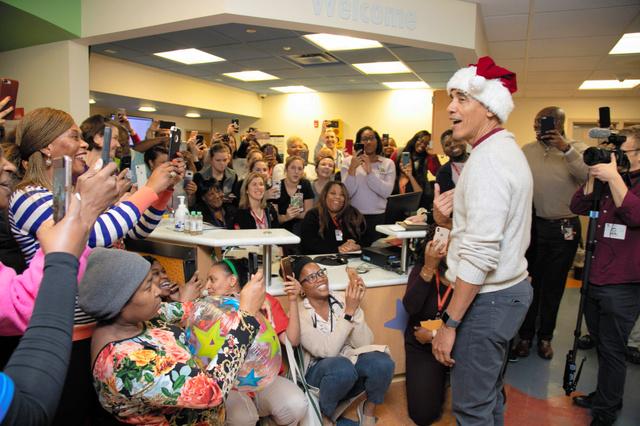 ワシントンにある小児科の病院で19日、子どもたちにプレゼントを渡した米国のオバマ前大統領=AFP時事