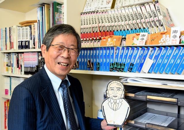敬愛する黒田清さんの似顔絵を手に。書棚に漫画『こちら大阪社会部』が並ぶ=2018年12月20日午後、大阪市北区、堀内義晃撮影