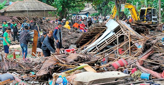 インドネシア・ジャワ島西部のチャリタで23日、津波の被害を受けた家屋を確認する住民ら=AP
