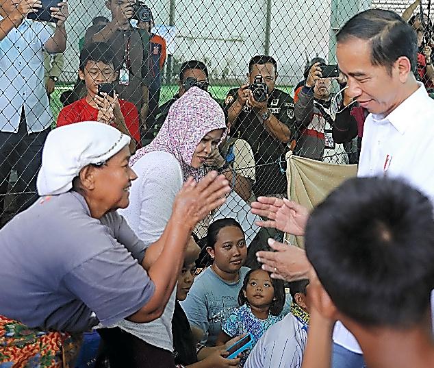避難所を慰問したジョコ大統領(右)に握手を求める被災者たち=パンデグラン
