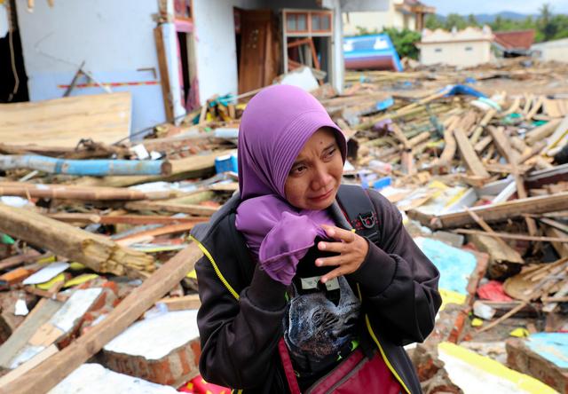 津波でがれきとなった自宅の前で目に涙を浮かべながら振り返るロディアトゥル・アラウィヤさん=2018年12月28日午後2時33分、スンブルジャヤ村、野上英文撮影